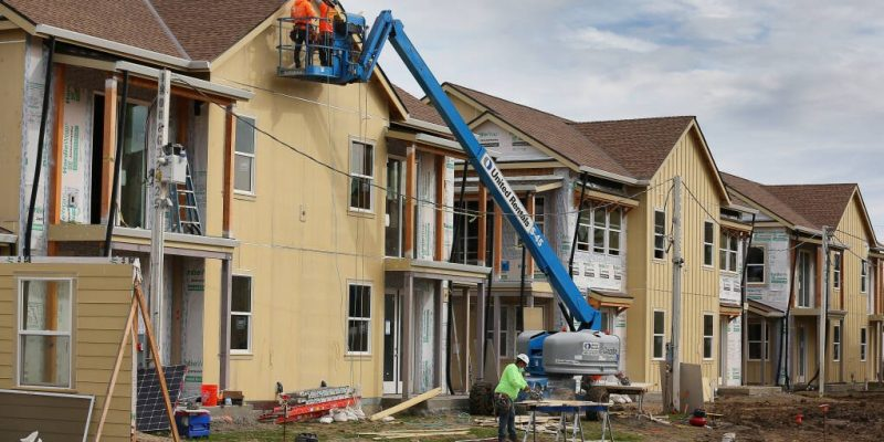 Construction workers place siding on a unit at Windsor Veterans Village in Windsor on Tuesday, February 9, 2021.  The project includes 60 affordable housing units for low-income veterans and their families.  (Christopher Chung/ The Press Democrat)